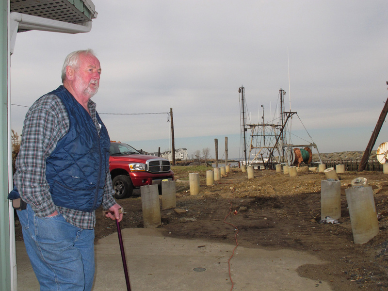 Joe Branin, manager of the Belford Seafood Co-op in Middletown, N.J., walks across sand where the commercial fishing port's dock used to be before Superstorm Sandy destroyed it, leaving only rows of support pilings. Pounding waves also gutted a popular restaurant and ripped away all five garage doors and parts of the exterior of office and storage buildings.