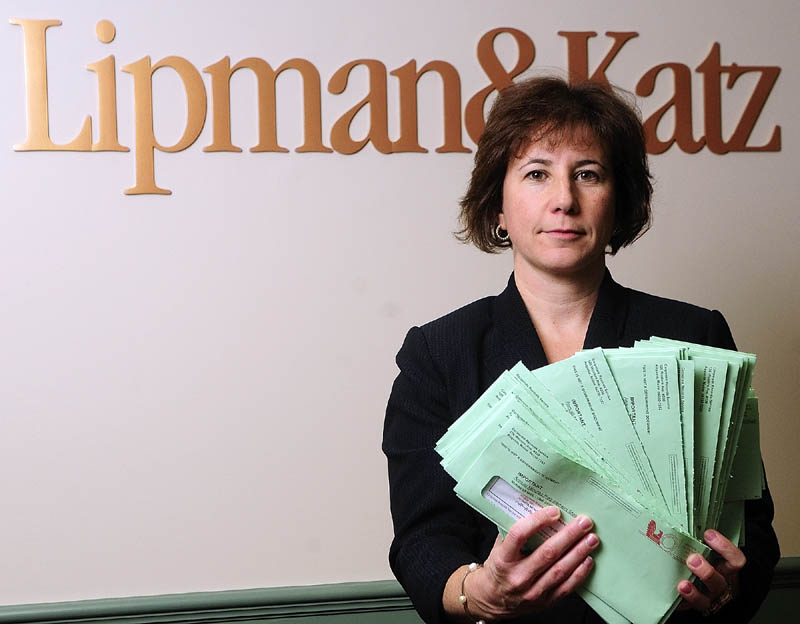Attorney Karen Boston displays about 60 letters received at the Lipman & Katz law firm on Wednesday in Augusta. The letters asked for corporate directors' names, addresses and $125 from