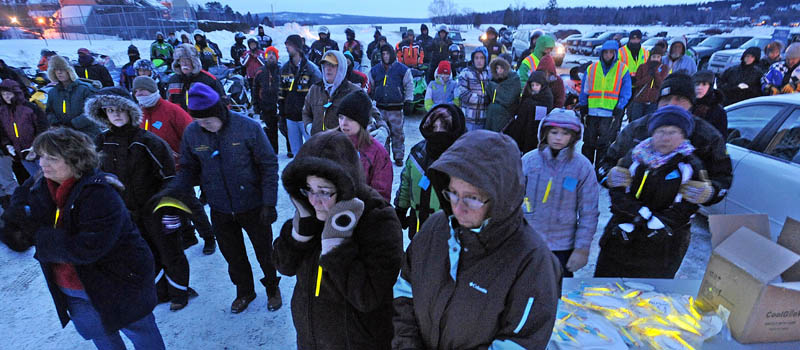 People gather and try to stay warm during a prayer during the Torch Light Snowmobile Safety Vigil in Rangeley Friday night.