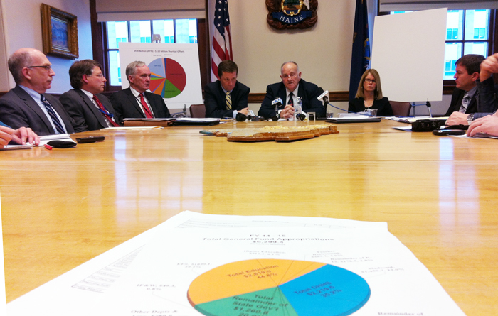 Gov. Paul LePage's budget officer Sawin Millett, center, briefs members of the news media on the governor's $6.2 billion budget proposal. DHHS commissioner Mary Mayhew and education chief Steve Bowen are on the right.
