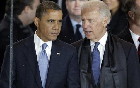President Barack Obama talks with Vice President Joe Biden in the presidential box during the inaugural parade down Pennsylvania Avenue en route to the White House Monday, in Washington. White House Inauguration