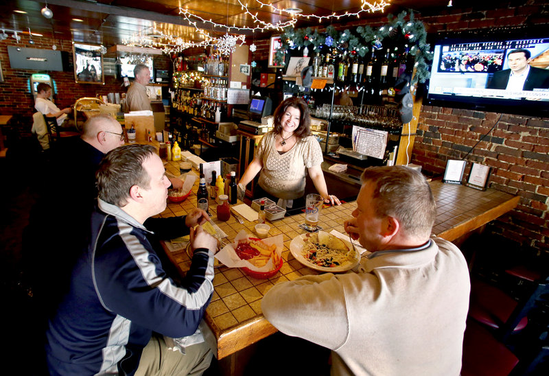 Rosie's bartender Barbie Asali visits with Jamie Hilton of Falmouth, left, and Peter Doyon of Cape Elizabeth.