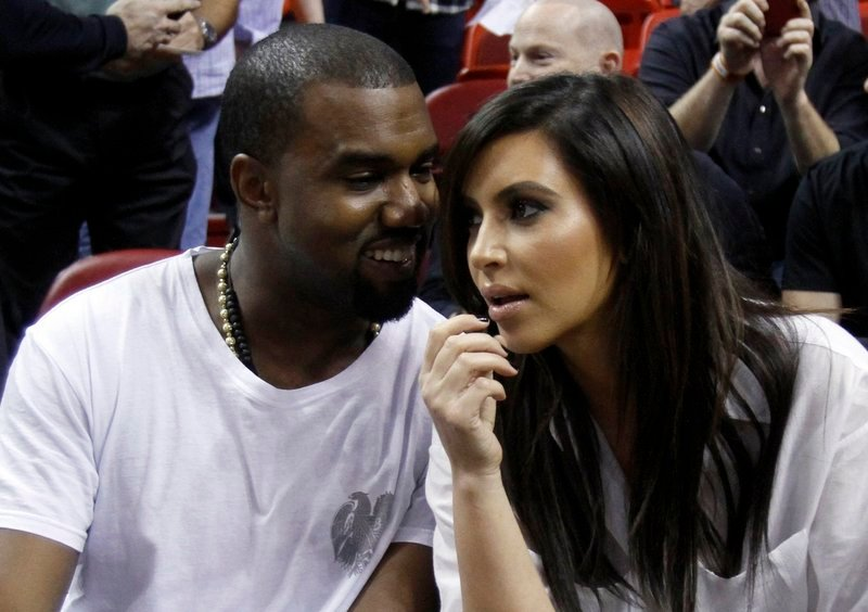 Kanye West, left, talks to Kim Kardashian before an NBA basketball game between the Miami Heat and the New York Knicks on Dec. 6 in Miami.