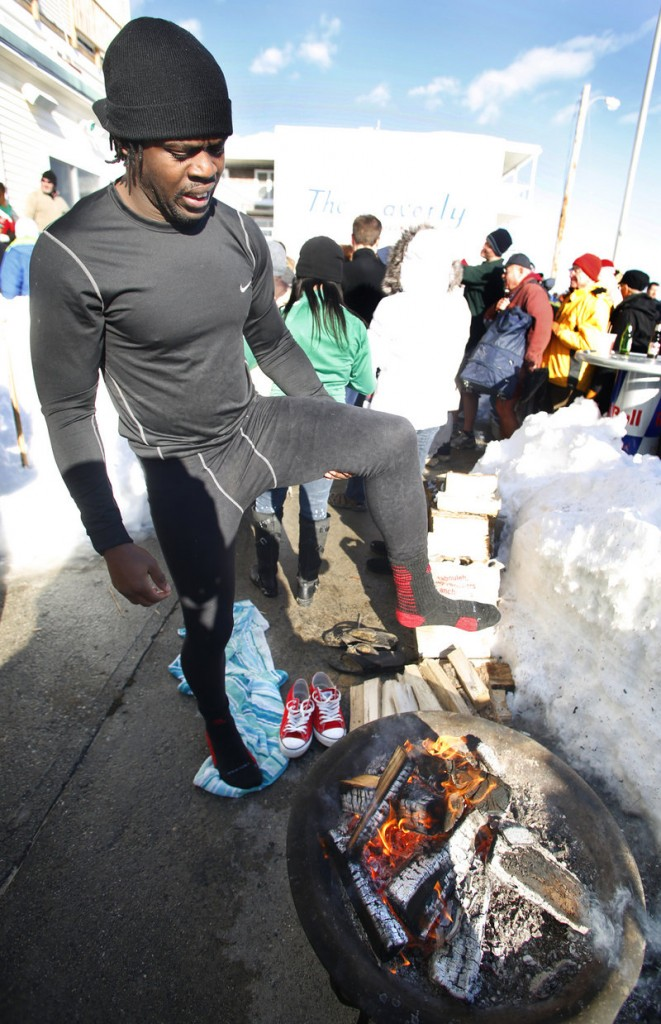 Edwin James of Killeen, Texas, warms his feet by the fire at The Brunswick after taking the plunge during the Lobster Dip to benefit Special Olympics Maine on Tuesday.