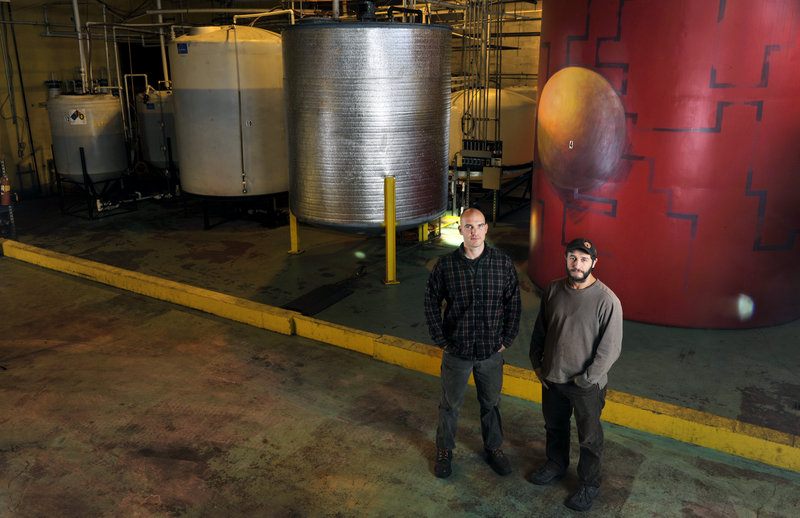 Matt Pemberton, left, of Maine Standard Biofuels and founder Jarmin Kaltsas stand near the company's colorful holding tanks. Its Portland plant now produces 300,000 gallons a year, but is capable of 1.5 million gallons.