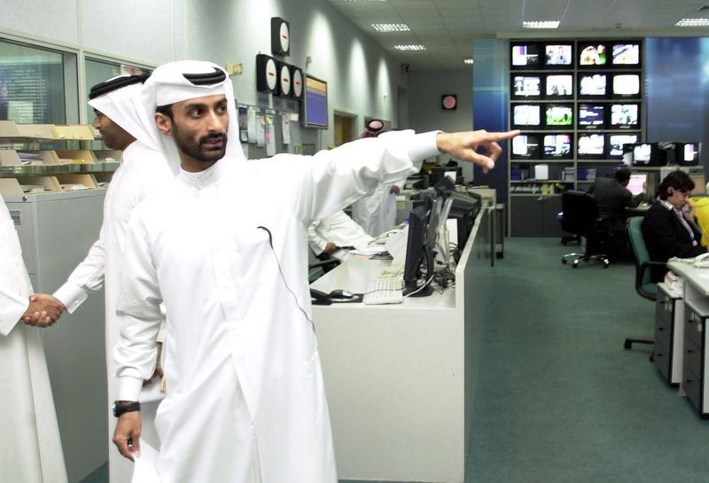 A Qatari staff member of al-Jazeera points out the newsroom of the TV network in Doha, Qatar, in February 2005.