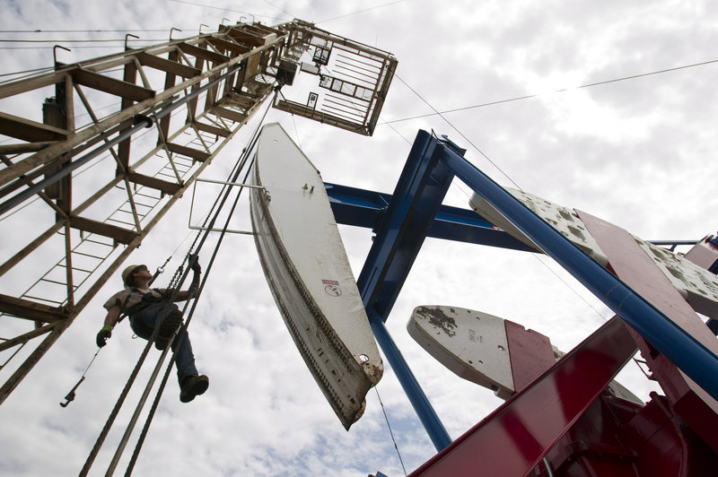 A worker hangs from an oil derrick in North Dakota, which set an oil-production record for the fifth year in a row in 2011.