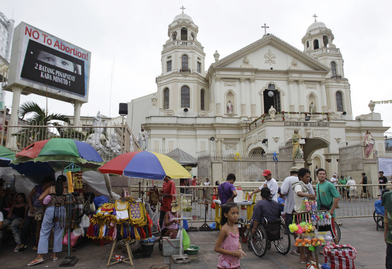 """""""No to abortion"""" flashes on an electric sign outside the Minor Basilica of the Black Nazarene in Manila on Thursday. Catholic leaders consider the new law that provides state funding for contraceptives an attack on the church's core values."""