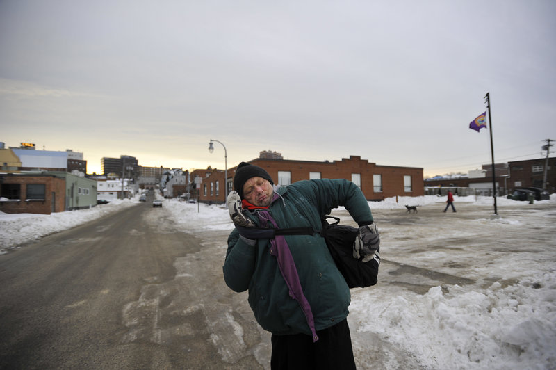 Charles Jones, 55, struggles to sling his bags up onto his shoulder while walking on Alder Street Friday morning. Jones suffers from bulging discs in his back, and says that being homeless –and having to carry his belongings – exacerbates his injury.