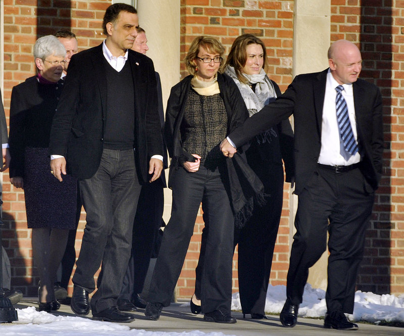 Former U.S. Rep. Gabrielle Giffords, center, holds hands with husband Mark Kelly as she leaves Town Hall in Newtown, Conn., Friday after meeting with Newtown officials.