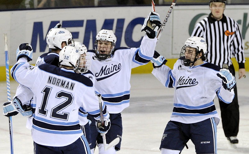 Maine players celebrate their first goal of the game, a first-period tally by Joey Diamond that tied the score at 1-1. A power-play goal by Maine's Ryan Lomberg with about six minutes remaining sealed the win on Friday night.