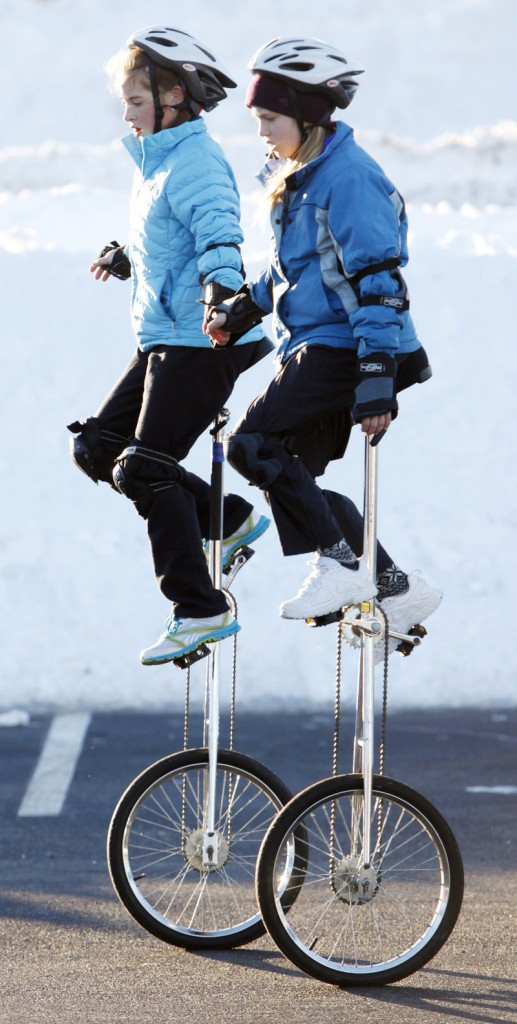 Grace Murphy, left, and Julia Booth-Howe practice on their unicycles at the Scarborough High School parking lot Saturday.