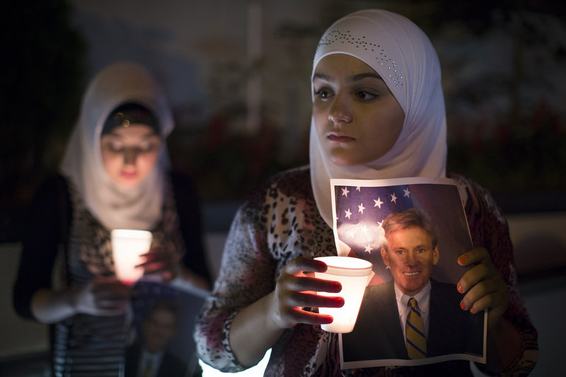 """A girl holds a photo of slain U.S. Ambassador to Libya Christopher Stevens at a vigil outside the Libyan Embassy in New York on Sept. 13. When Stevens was killed, Republicans soon doled out blame, but following the Newtown massacre, conservatives said that talk of new limits on firearms was an effort """"to 'capitalize on a tragedy,'"""" a reader says."""