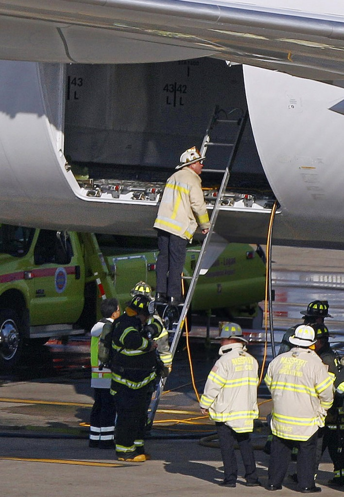 Boston firefighters examine the cargo hold of a Japanese airliner that sustained a small electrical fire following a flight from Tokyo to Logan International Airport on Monday.