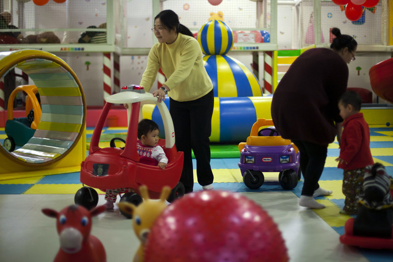 Parents play with their children at a kids' play area in a shopping mall Thursday in Beijing. In China, a law generally limits urban families to having just one child.