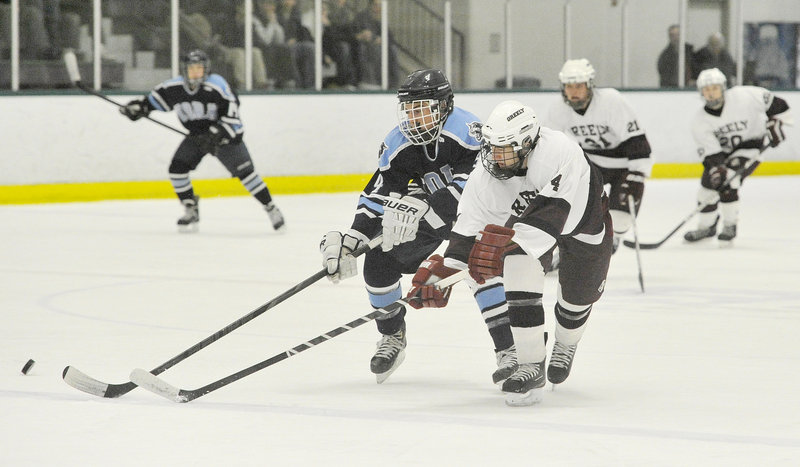 Miles Shields, right, of Greely and Derek Neal of York chase after the puck during Greely's 13-0 victory Thursday night at Family Ice Center.