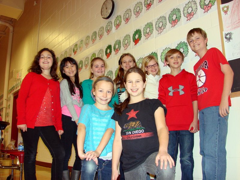Wells Junior High School students recently completed a project to discover the final resting places of military veterans in Wells. Among the fifth-graders who took part are, front from left, Rielly Delucca and Meredith Bogue, and back from left, Hannah Wrigley, Kaitlyn Chrisemer, Erin Dinmore, Savanah Wilder, Abigail Booth, Zachary Steere and Nathan Chandler. The students also created paper wreaths, shown behind them, bearing the names of the deceased veterans.