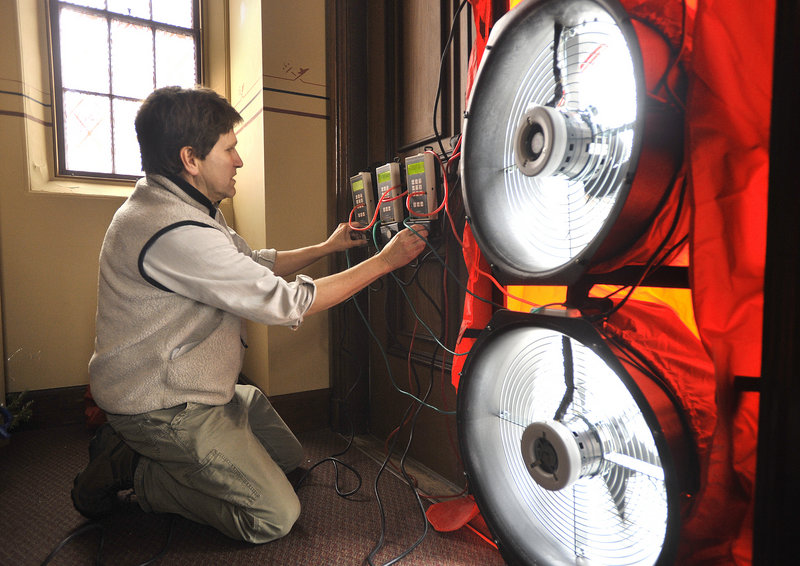 Energy consultant DeWitt Kimball operates large fans used to de-pressure the interior of the church as determine how much air is leaking from the building on Friday, January 11, 2013.