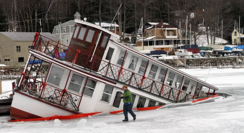 Owner of the MV Kearsarge, Peter Fenton, examines his sinking dinner cruise ship in Sunapee Harbor Friday, Jan. 11, 2013 in Sunapee, N.H. Authorities said the ship started to go under at about 7:45 p.m. Thursday, and part of the lower deck at the back of the boat was under water Friday morning. It was not immediately known what caused the problem. The MV Kearsarge has been taking visitors around Lake Sunapee from May through October for over 30 years.