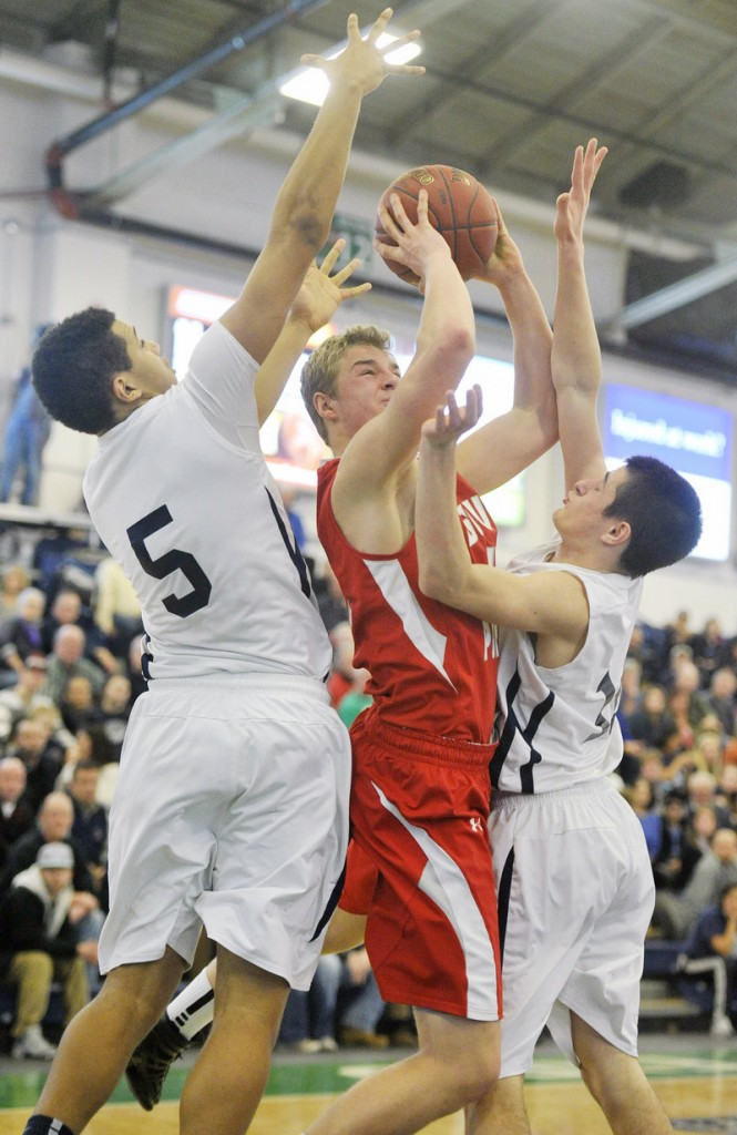 Ben Burkey of South Portland attempts to get off a shot Friday night while defended by Matt Talbot, left, and Justin Zukowski of Portland at the Expo.