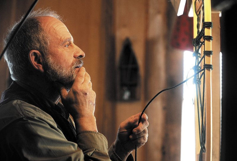 Dave Giampetruzzi laces a one-of-a-kind snowshoe in his cabin at Pine Grove Lodge.