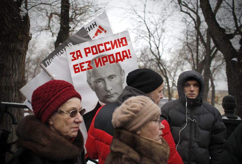 """A poster of Russian President Vladimir Putin with the words """"For a Russia without Herod!"""" is seen Sunday at a Moscow rally against a law barring Americans from adopting Russian children. The biblical ruler Herod ordered the massacre of infants in Bethlehem at the time of Jesus."""