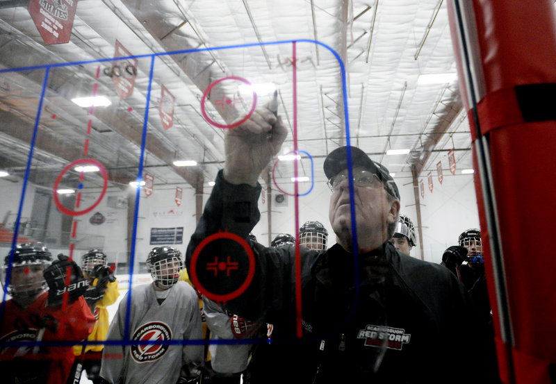 """Scarborough High School boys' hockey coach Norm Gagne, 66, and now in his 38th year as a coach, draws up plays during a practice at MHG Ice in Saco. On coaching, he said: """"It blows my mind to see how much it's changed."""""""