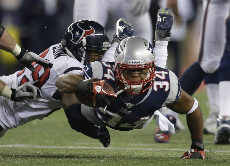 Shane Vereen stretches for extra yardage while being tackled by Houston's Glover Quin. Vereen scored three touchdowns for the Patriots.