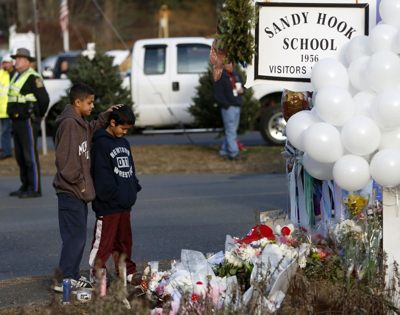 Thomas and Steven Leuci, a pair of 13- and 9-year-old brothers, pay respects at a memorial to victims at Sandy Hook Elementary School last month in Newtown, Conn. The town must decide on what to do with the school – one option is to demolish it and rebuild.