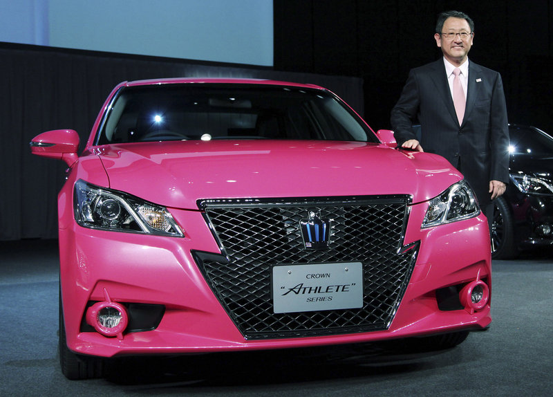 Toyota President Akio Toyoda stands next to the company's redesigned Crown sedan, which was unveiled earlier this month. The car is not sold in the U.S. and probably never will be, Motor Trend says.
