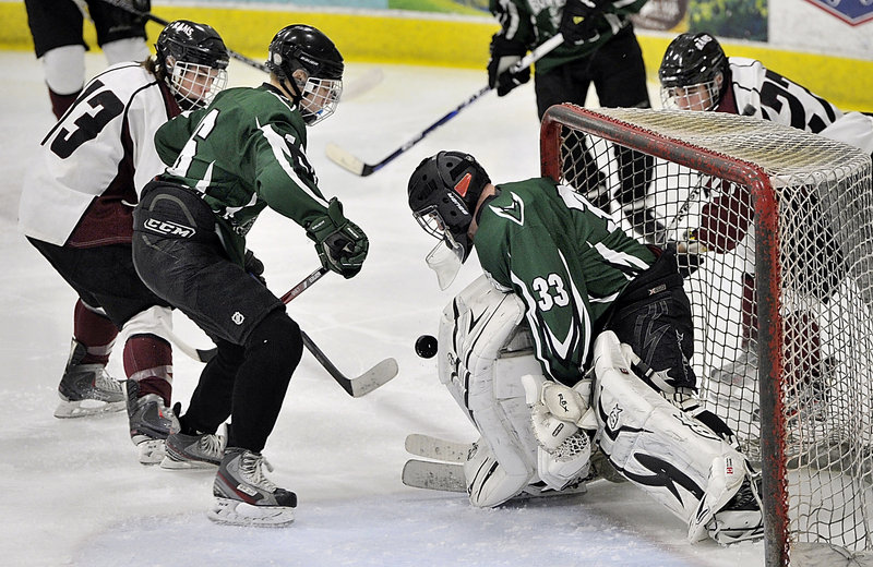 Bonny Eagle goalie Garrett McElrath makes a pad save on a shot from close range as defenseman Justin Miles tries to fend off Gorham's Tucker Buteau Monday night at USM Ice Arena in Gorham.