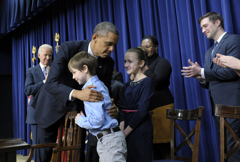President Barack Obama, accompanied by Vice President Joe Biden, left, hugs 8-year-old letter writer Grant Fritz during a Wednesday news conference on proposals to reduce gun violence at the White House.