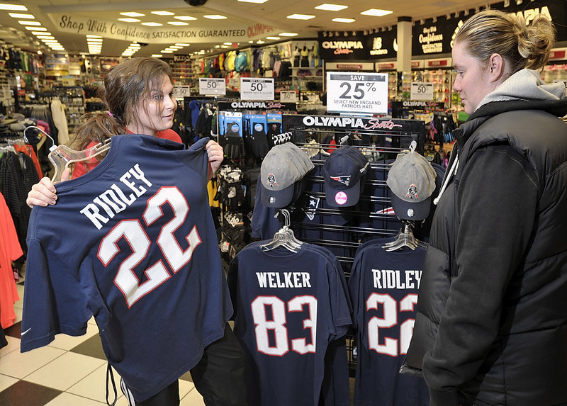 Olympia Sports manager trainee Jacqueline Bevier, left, helps regular customer Charissa Kennard from Conway, New Hampshire, explore the store's collection of Patriots souvenir clothing options at the Maine Mall store. Photographed on Wednesday, January 16, 2013.