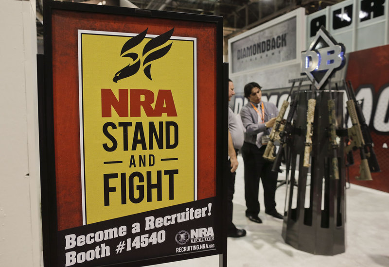 A National Rifle Association poster decorates a booth at the 35th annual