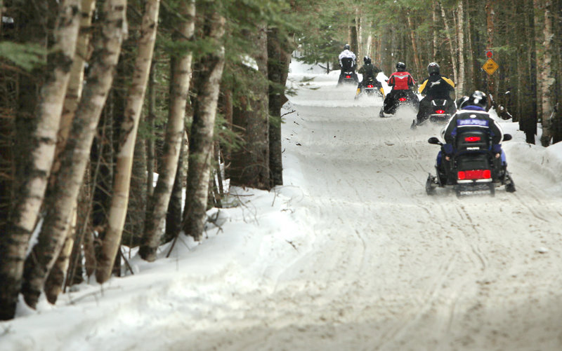 Snowmobilers ride along ITS 84 in Oquossoc on Jan. 12.