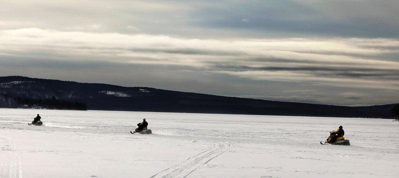 Snowmobilers head across a cove on Rangeley Lake in Rangeley on Jan. 12.