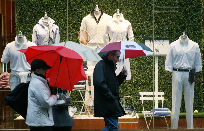 Shoppers pass a Brooks Brothers display window in New York. Seventy percent of the retailer's suits are made in a Massachusetts factory.