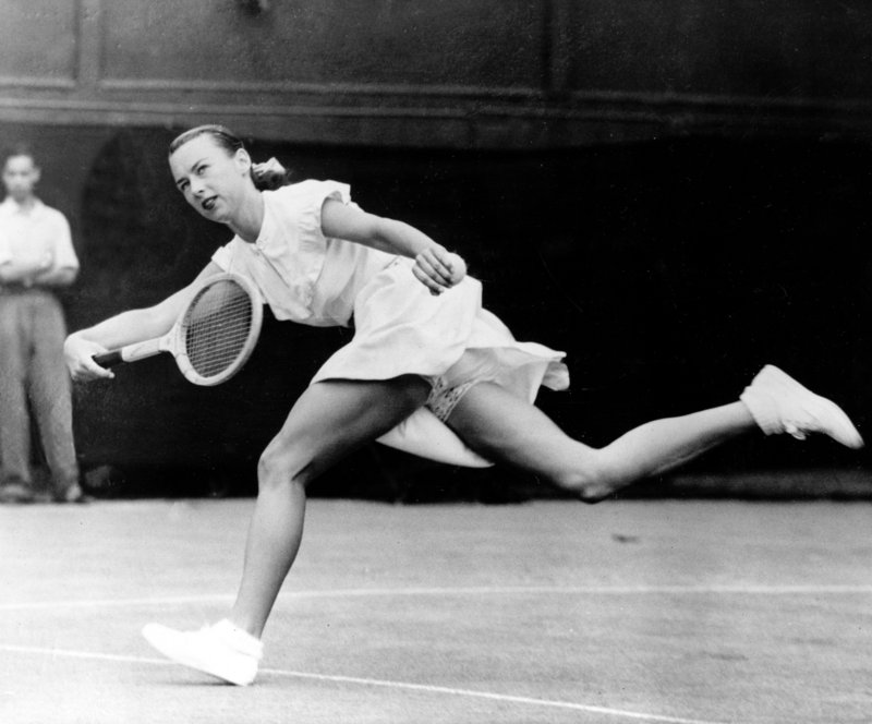 "Gertrude ""Gussie"" Moran races to make a shot in 1949 at Wimbledon in London. She lost the match, but her fashion statement appeared on magazine covers around the world."