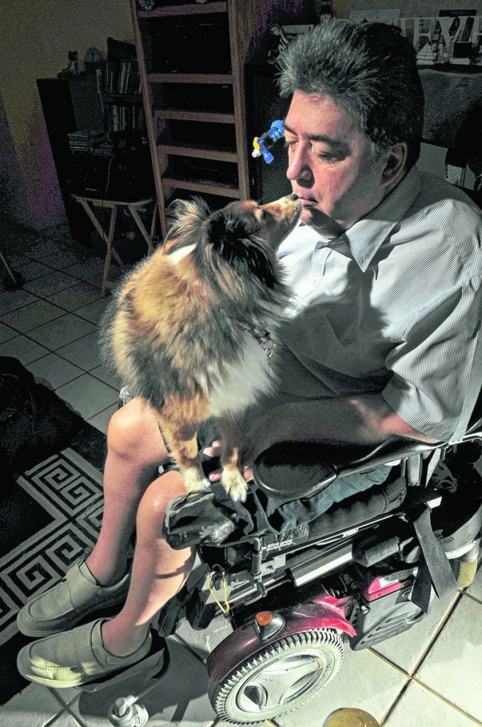 David Aldrich, pictured last month in Delray Beach, Fla., uses his mouth to give a biscuit to his dog, Skipper. Aldrich was left a quadriplegic and blind after a fall in 2002.