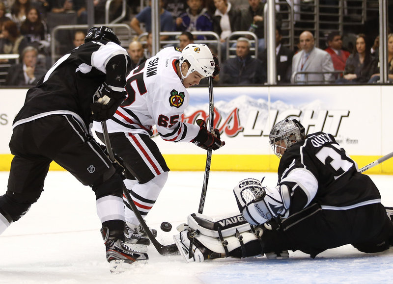 Chicago's Andrew Shaw fights for a loose puck while Los Angeles goalie Jonathan Quick and Alec Martinez go for the clear. Chicago won, 5-2.