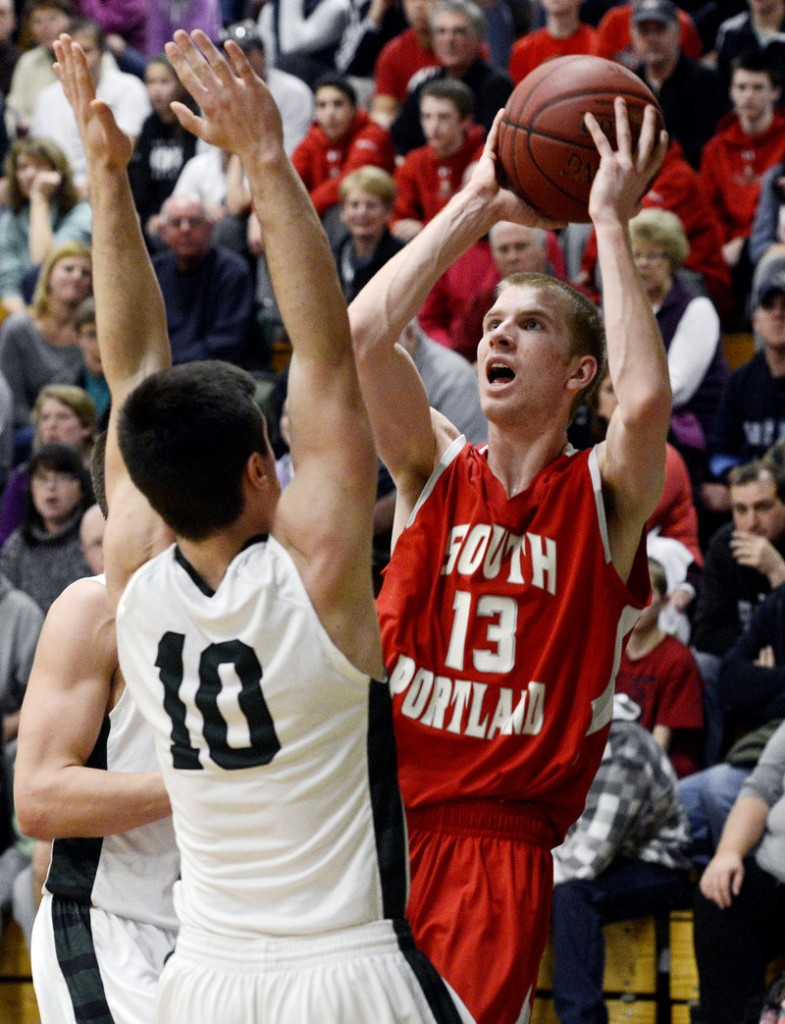 Tanner Hyland take a shot over Bonny Eagle's Zach Dubiel in Monday's game. Hyland had 23 points and hit two buzzer beaters in the Riots' win.