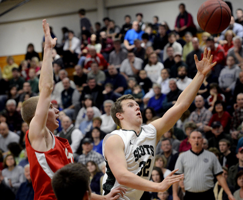 CJ Autry of Bonny Eagle drives to the basket as South Portland's Tanner Hyland moves in on defense Monday. Autry had six points and five rebounds in the Scots' double-overtime loss at home.