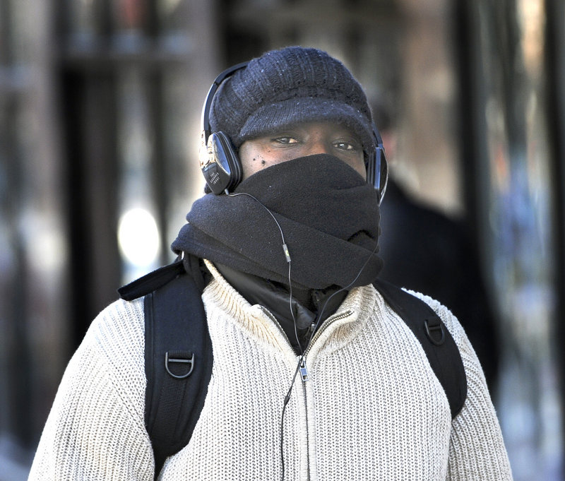 Orphee Baranshamaje from Portland is one of many pedestrians who braved the cold and wind Tuesday, Jan. 22, 2013.
