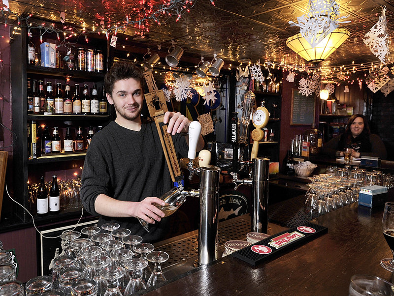 Assistant manager and bartender Thomas Henley draws a beer from one of six taps that feature Allagash Brewing beers, among others, at Mama's CrowBar.
