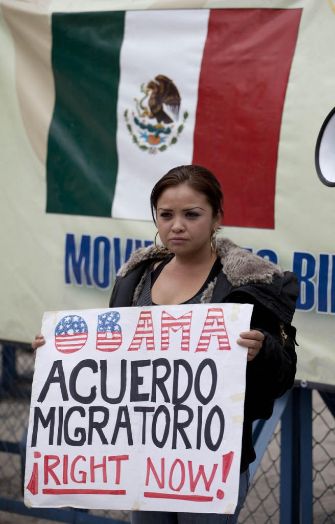 """A migrants' rights activist holds a sign that reads, in Spanish, """"Obama, migration agreement right now!"""" outside the U.S. embassy in Mexico City."""
