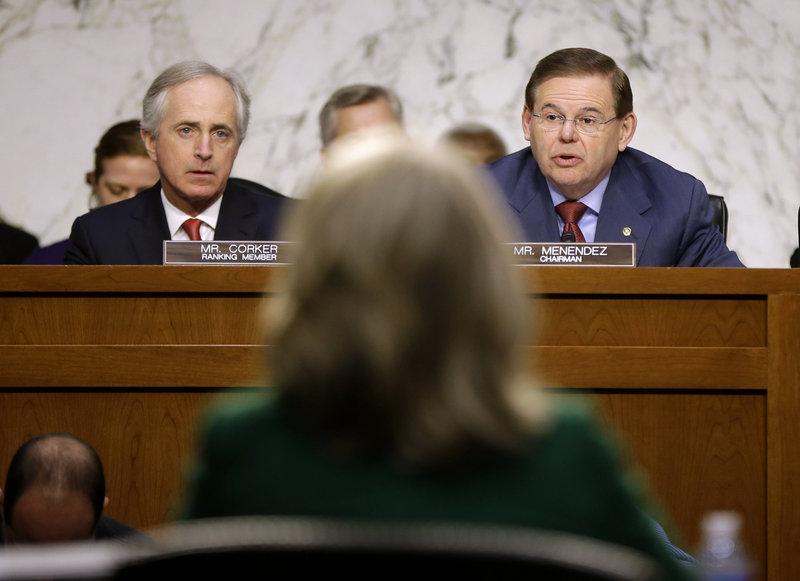 Secretary of State Hillary Rodham Clinton, back to camera, tangles with the Senate Foreign Relations Committee's Sen. Bob Corker, R-Tenn., left, and Sen. Robert Menendez, D-N.J.