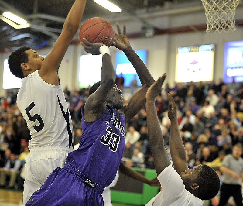 Labson Abwoch of Deering powers his way to the basket Thursday night as Matt Talbot, left, and Steve Angelo of Portland attempt to stop him. Abwoch scored 13 points but Portland came away with a 44-37 victory at the Portland Expo.