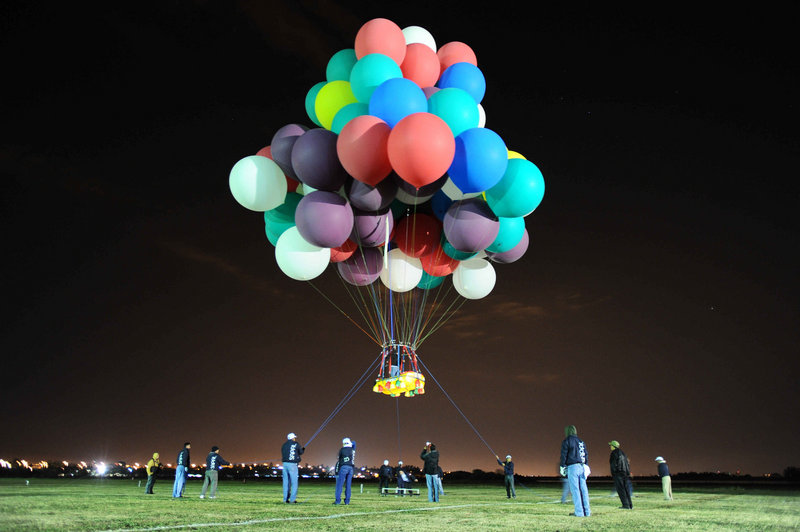 Jonathan Trappe takes off on a test flight in a Portland-made dinghy attached to balloons at the Leon International Balloon Festival in November in Leon, Mexico. He says he will need 365 balloons to keep him aloft for a trip across the Atlantic this summer.