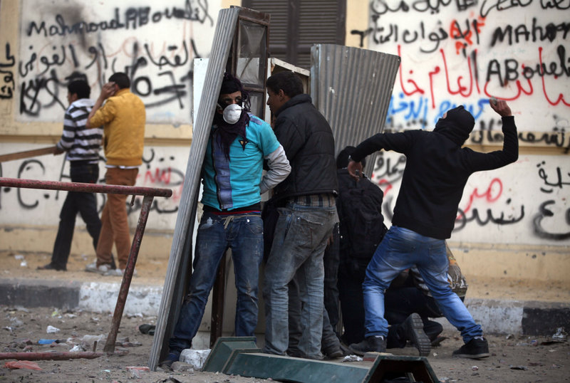 Egyptian protesters take cover as they clash with riot police near Cairo's Tahrir Square on Friday. Two years after Egypt's revolution began, the country's schism has flared again.