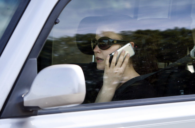 """A motorist uses a cellphone while driving on I-295 in Portland. A recent survey shows a """"do as I say, not as I do"""" attitude when it comes to cellphone use by drivers."""